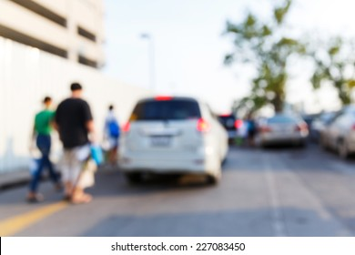 Abstract blurred people and car in parking area