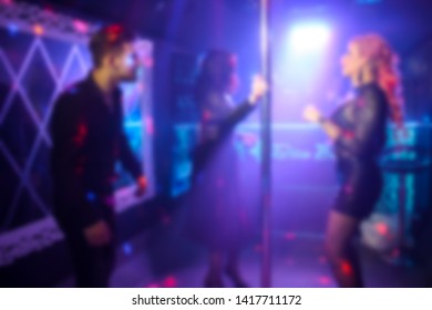 Abstract blurred people dancing in the party in the night club. Neon disco lights background.
