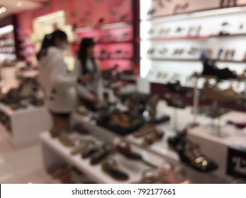 Abstract blurred people shopping shoe shop in department store. Defocused blur background.