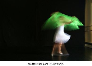 Abstract blurred photo of young ballet dancer in white dress on black background
