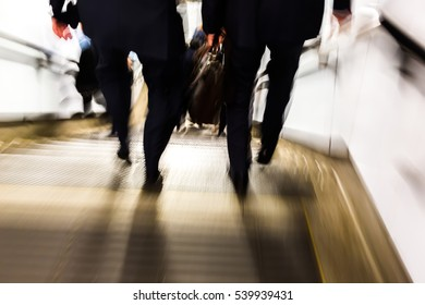 abstract blurred picture of commuters walking downstairs of an underground station