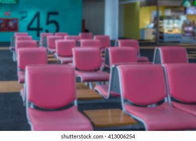 Abstract blurred of red leather seat at gate in airport terminal for passenger departure