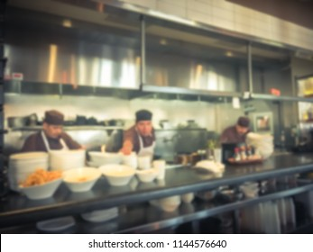 Abstract blurred restaurant chefs cooking in the open kitchen of Asian restaurant. Customer can see cooking preparation at food counter