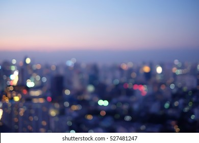 abstract blurred sky night city building of downtown construction with circle round light background with lens flare effect.