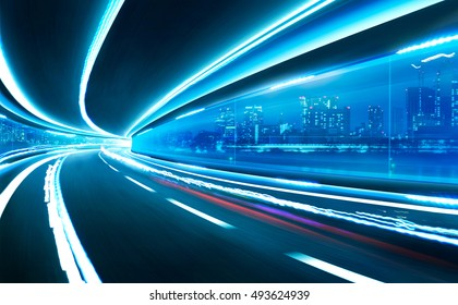 Abstract blurred speed motion road in glass tunnel over the city - Shutterstock ID 493624939