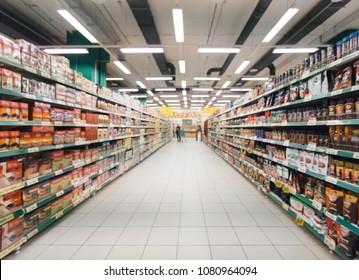 Abstrakter, unscharfer Supermarktgang mit bunten Regalen und unerkennbaren Kunden als Hintergrund