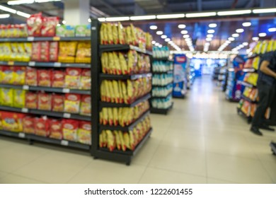 Abstract blurred supermarket aisle with colorful shelves and unrecognizable customers as background. Fruit and vegetable section