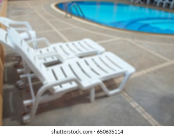 Abstract blurred swimming pool with chaise lounge on terrace.