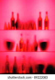 Abstract blurred vine bottles and glasses on shelf, pink color
