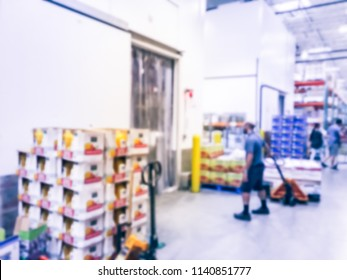 Abstract blurred worker with manual forklift stockpile goods near cold storage room in wholesale store