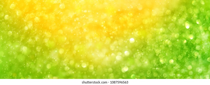 abstract blurred yellow-green beautiful shiny background with light spots. soft selective focus. long wide banner