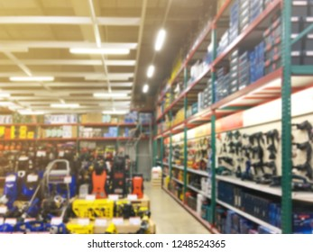 Abstract blurry background of power tools on shelf display at shop. Hardwear store interior.