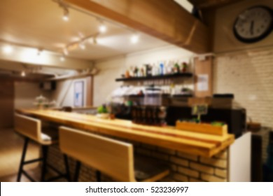 Abstract blurry bar counter with chairs in empty comfortable restaurant.