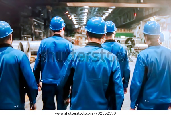 Abstract, blurry, bokeh background, image for the background. People in overalls in production