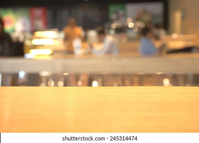 Abstract blurry coffee shop counter with wooden table in foreground background