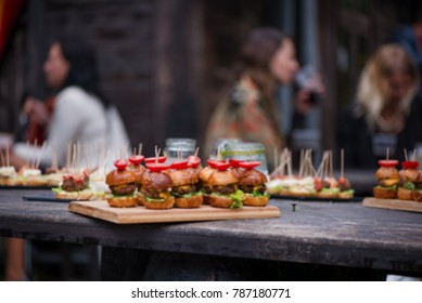Abstract blurry food background. Small burgers with meat, salads cheese and tomatoes on wooden plate during summer barbecue party outdoors. Friends preparing food, chatting and having drinks together