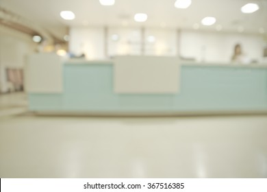Abstract blurry hospital reception area with unrecognizable receptionist