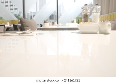 Abstract blurry restaurant with blurry green large tree visible outside windows in background