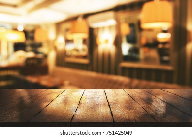 Abstract blurry restaurant interior background with empty wooden table. Mock up