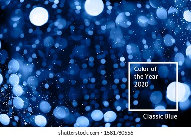 Abstract bokeh background with beautiful shiny festive blue lights creating a magic atmosphere in main color of the year 2020.