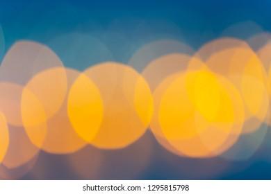 Abstract boken defocused bright lights in orange hues against blue sky