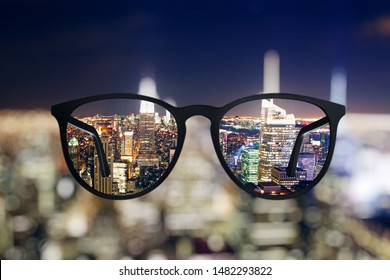 Abstract bright night city view through eyeglasses. Blurry background. Vision concept