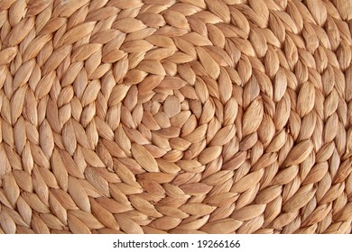 Abstract brown background. Spiral pattern of a straw mat