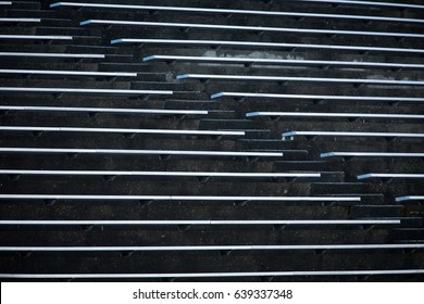 Abstract brutal modernism concrete sports stadium with horizontal rows of aluminum bleacher benches divided by diagonal aisle of stairs