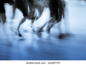 abstract business concept, walking people legs on city street blur.
