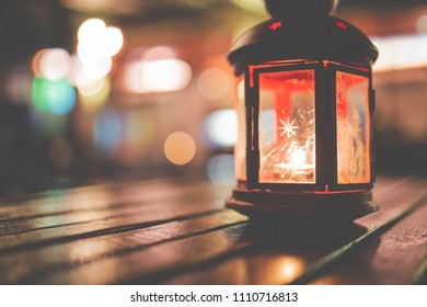 Abstract candle lantern light on wood table in blur bokeh pub restaurant dinner background concept for ramadan kareem night life, wooden tabletop dark indoor counter, happy kid mubarak.