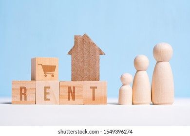 Abstract cardboard house next to an arbitrary family: mom, dad, baby word buy on cubes for rent. Housing rental concept. Close up.