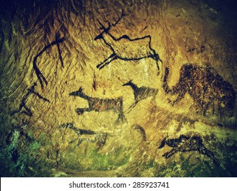 Abstract children art in cave. Black carbon paint of human hunting on sandstone wall, copy of prehistoric picture.Prehistoric drawings in cave. Bison, mammoth, deer, caveman. Primitive neanderthal art