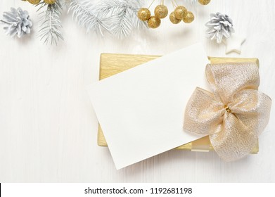 abstract christmas background, white sheet of paper lying among small decorations on white wooden desk. Flat lay mockup for your art, picture or hand lettering composition copy space, top view