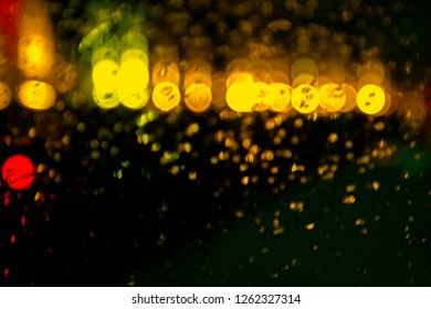 abstract Christmas background-bright lights of garlands on water drops on the glass. water drop on the obscured glass abstract color