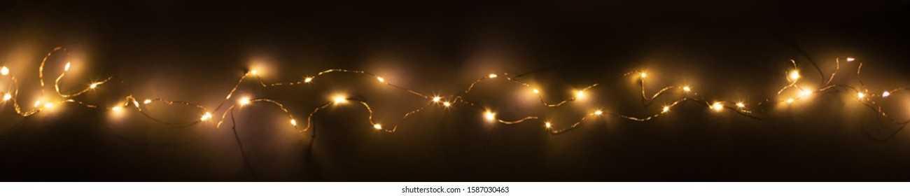 Abstract christmas led lights on dark  background. Blurred glowing light bulb garland,  layer for screen mode overlays to light up the bulbs. Festive concept banner