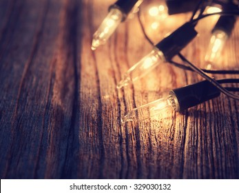 Abstract Christmas lights on dark wooden background and free text space.: Vintage style and filtered process.