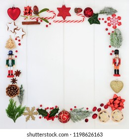 Abstract Christmas square wreath with a selection of traditional symbols including food, flora and tree bauble decorations on white wood background. Top view.