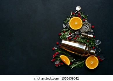 Abstract christmas tree made from ingredients and props for making festive cocktail on a black slate, stone or concrete background. Top view with copy space.