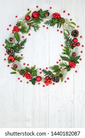 Abstract Christmas wreath with red bauble decorations, holly, pine cones, mistletoe, snow covered spruce fir and loose red berries on rustic white background with copy space.