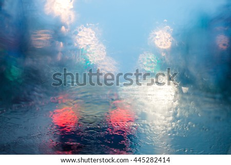 Abstract circular bokeh motion lens blur backround of city and street light on rainy day