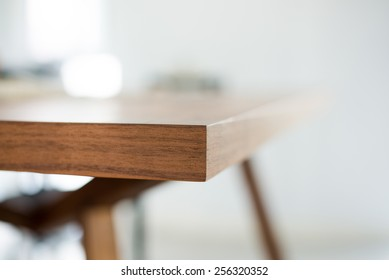Abstract classic design beautiful dark brown wooden dinning table edge and leg. modern furniture as a blur background.