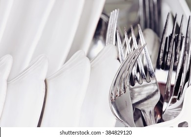 Abstract of clean forks and dishes inside of a dish washing machine. Extreme shallow depth of field with selective focus on fork.