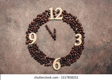 Abstract clock made of roasted coffee beans on a dark brown rustic background. New Year concept. Five minutes to twelve