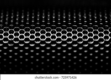 Abstract close up macro perforated metal texture in black and white hole pattern.