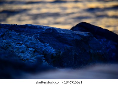Abstract closeup of dark blue shadow on large rocks with gently rippling ocean water in the background and faded texture of beach sand