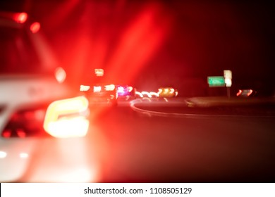 Abstract closeup of many cars in traffic moving in dark night evening colorful colors, street lights, red braking shape