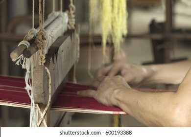Abstract closeup of pair of hands sewing cloth using traditional large sewing machine which was commonly used in northen part of Thailand
