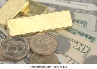 Abstract closeup pile of gold bars over dollar coins and banknotes