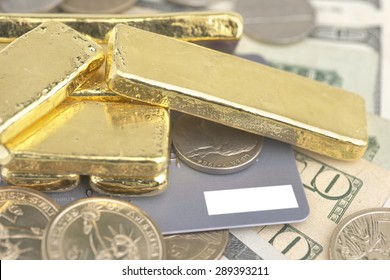 Abstract closeup pile of gold bars over dollar coins, banknotes and credit card