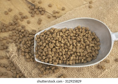 Abstract closeup of premium grade dog food spill all over with half full spoon of food over agriculture sack on top of wooden board